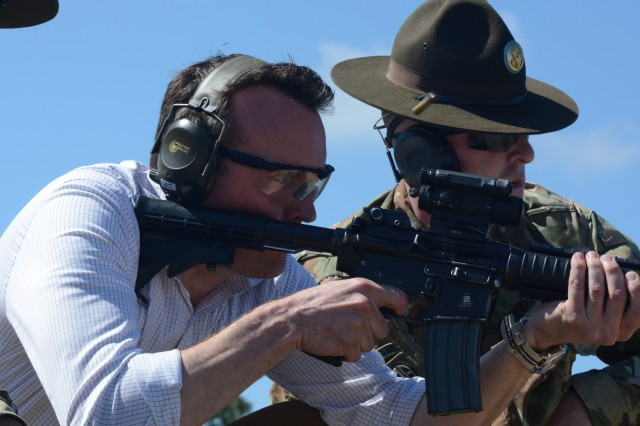 Staff Sgt. Charles Flores and Staff Sgt. Christopher Demaria, drill sergeants with Bravo Company, 3-60th Infantry Regiment call targets to Secretary of the Army Eric Fanning as he fires an M-4 rifle during his tour of the post.