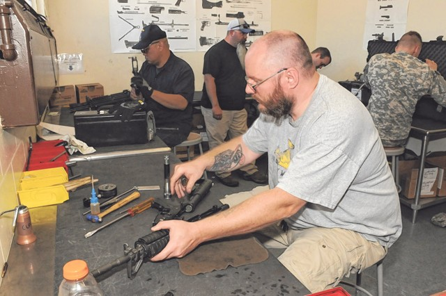 Dave Rybac reassembles an M4 rifle after a quarterly inspection at the 3rd Chemical Brigade Monday.