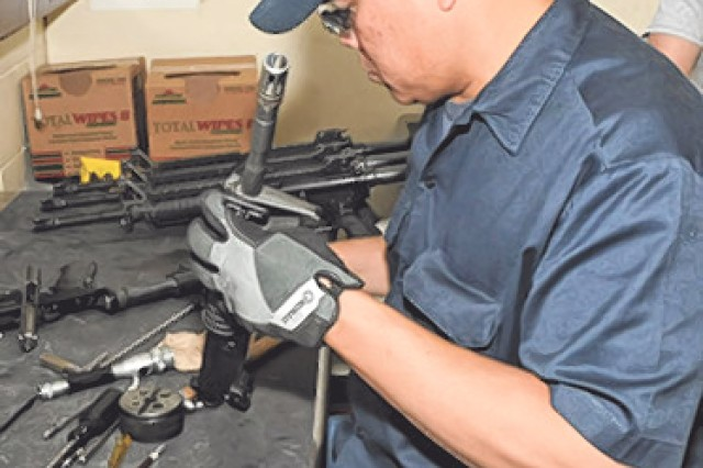 Robert Castiento inspects an M4 rifle piece-by-piece to check serviceability, functionality and safety.