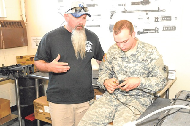 Jimmy Childers, optics technician, informs Pfc. Chris Jolly, a computer/detection systems repairman from the Wisconsin National Guard, about the process for inspecting an M68 optic sight.