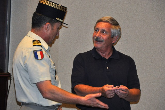 Retired Maj. Robert Cassella is presented France's Brevet Militaire de Parachustiste, known as French jump wings or the military parachutist badge, by French Liaison Officer Col. Nicolas Auboin June 6 in a ceremony at the Lewis and Clark Center at Fort Leavenworth, Kan. Cassella performed the jump that earned him the wings in 1975.