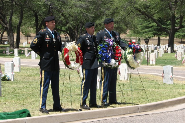 From left, Sgt. 1st Class Artez R. Briseno, Sgt. 1st Class Adam C. Tripses and Sgt. 1st Class William F. Laster, all members of the Sgt. Audie Murphy Club (SAMC), stand at the position of parade rest following the placement of wreaths May 30 during the Memorial Day ceremony at Old Post Cemetery.