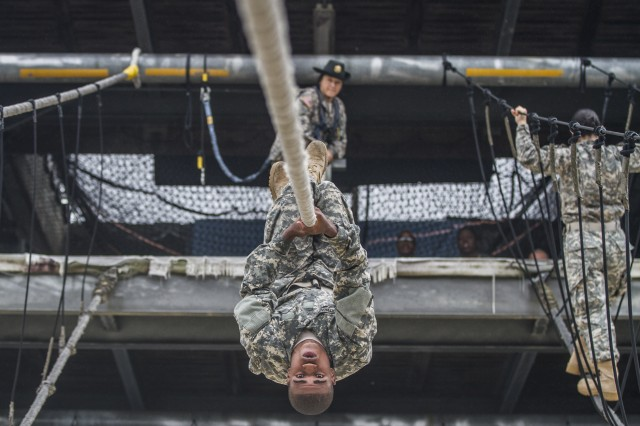 After losing his balance on a rope bridge obstacle, a Soldier in Basic Combat Training with E Company, 2nd Battalion, 39th Infantry Regiment, attempts to complete the task by using pure upper body strength to shimmy across to the other side with his Drill Sgt. looking on, Oct. 28, 2015. Soldiers in Basic Combat Training must complete all tasks at Victory Tower on Fort Jackson, S.C., which also boasts a 40-foot repelling wall, in order to graduate.