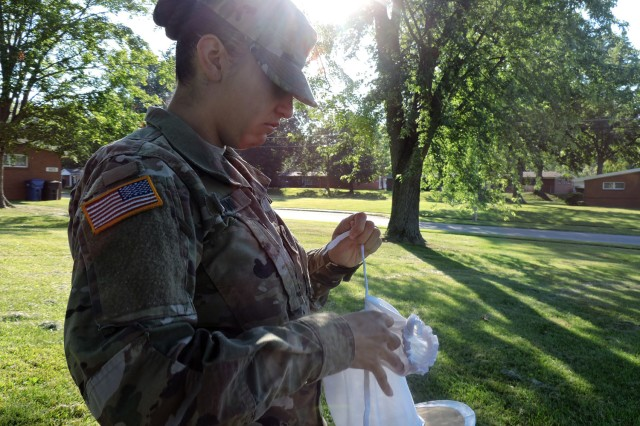 Spec. Alicia Alviani, a preventive medicine specialist, checks a CDC light trap that was set in a residential area on Fort Knox to capture mosquitos. When a trap does capture mosquitos the trap is sent to Public Health Command for testing and monitoring.