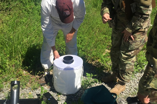 James Butler, visiting entomologist from Public Health Command-Atlantic, shows Capt. Taylor Hirschey how the BG-Sentinel mosquito trap works.  This type of trap is used to collect Aedes mosquitos, the potential carriers of Zika.