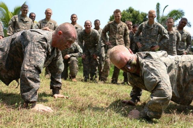 U.S. Army Spc. Jared Butler (left), infantryman of Bravo Company, 3rd Battalion, 7th Infantry Regiment, 2nd Infantry Brigade Combat Team, 3rd Infantry Division, and 1st Lt. John Kneppler (right), platoon leader of Co. B, perform push-ups to break a tie for best performance during an obstacle course while their platoon cheers for them during Jungle Warfare School in Gabon, June 8, 2016. Soldiers are attending the French Jungle Warfare School as part of U.S. Army Africa's exercise Central Accord 2016, an annual, combined, joint military exercise that brings together partner nations to practice and demonstrate proficiency in conducting peacekeeping operations.