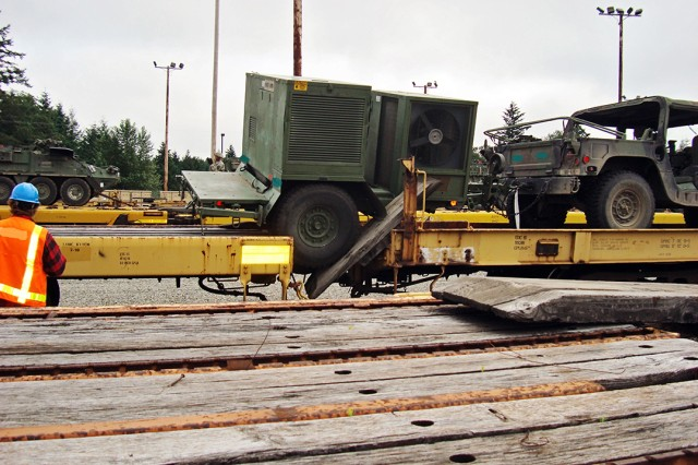 A railroad crewmember observes a vehicle that fell between railcars during loading because the spanners were not secure.