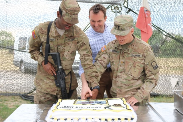Secretary of the Army Eric Fanning, Chaplain (Maj) Brian Smith, and Pvt. Tairay Warren cut the cake for the 241st Army Birthday, June 14, Torun, Poland.