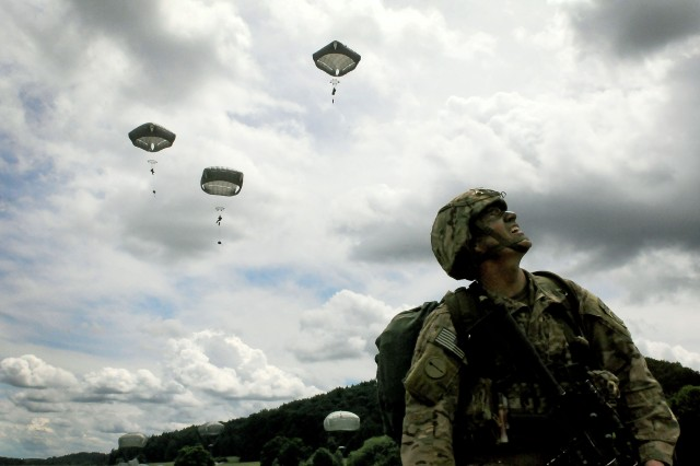 A soldier of the 82nd Airborne Division watches fellow paratroopers descend onto Hohenfels Drop Zone in Germany during Exercise Swift Response, June 15, 2016. Exercise Swift Response is one of the premier military crisis response training events for multi-national airborne forces in the world. The exercise is designed to enhance the readiness of the combat core of the U.S. Global Response Force -- currently the 82nd Airborne Division's 1st Brigade Combat Team -- to conduct rapid-response, joint-forcible entry and follow-on operations alongside Allied high-readiness forces in Europe. Swift Response 16 includes more than 5,000 Soldiers and Airmen from Belgium, France, Germany, Great Britain, Italy, the Netherlands, Poland, Portugal, Spain and the United States and takes place in Poland and Germany, May 27-June 26, 2016