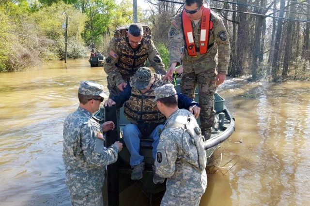 Members of the Louisiana National Guard's 2225th Multi-Role Bridge Company, 205th Engineer Battalion, help a man out of the bridge erection boat they used to check on residents who could not get out of their homes, in Ponchatoula, La., March 13, 2016. The current of the river, which had overcome its banks and flooded the road, was too strong for regular boat motors to battle.