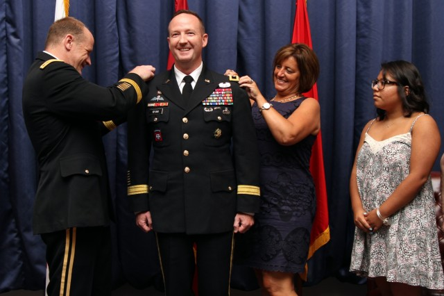 "Lt. Gen. Stephen Lyons (left), deputy, U.S. Transportation Command, Jennifer (second from right), and Madison (right), ""pin-on"" the new rank of Maj. Gen. to incoming Commanding General Kurt J. Ryan."