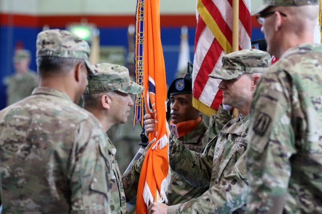 "Brig. Gen. Stephen Hager, incoming commander of the 335th Signal Command (Theater) (Provisional) and USARCENT G6, ""passes the colors"" to Command Sgt. Maj Rodney A Wionowsky, the top enlisted Soldier for the 335th Signal Command, during a change of command ceremony June 11 at Camp Arifjan, Kuwait. The command is responsible for communications and cyber capabilities across five time zones in the U.S. Army Central area of operations. (U.S. Army photo by Sgt. Brandon Hubbard, USARCENT)"