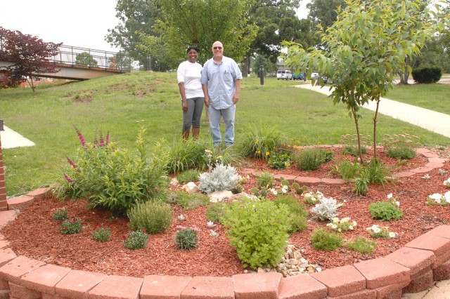 Allene Hodges, Davidson Fitness Center custodian, and John Olson stand in front of one of the flowerbeds at DFC. The pair worked together to improve the design and create a display that honored fallen heros, Soldiers and their Families.