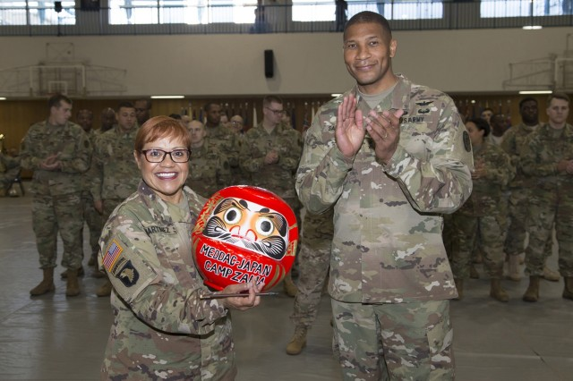Daruma Doll: One of the most popular talismans of good luck in modern Japan, the Daruma doll is received upon command. Col. Thirsa Martinez received this Daruma doll, two years ago, when she undertook the duties to lead, motivate and accomplish the MEDDAC-Japan mission. After successfully completing her command, Martinez filled in the other eye of the Daruma doll during the MEDDAC-Japan change of command ceremony was held on June 16 inside the Yano Fitness Center's gym. Martinez relinquished command of MEDDAC-J to Col. Andre R. Pippen. (U.S. Army photos by Kiyoshi Tokeshi)