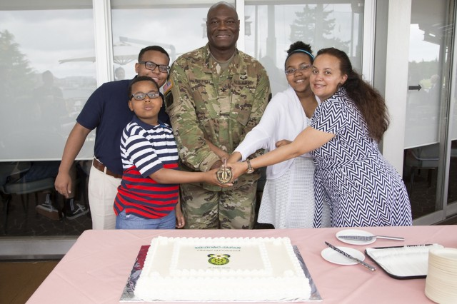 Col. Andre R. Pippen and his family poses for a picture before cutting the ceremonial cake after Pippen assumes command of MEDDAC-Japan during a ceremony held June 16 inside the Yano Fitness Center's gym on the Camp Zama installation. (U.S. Army photos by Kiyoshi Tokeshi)
