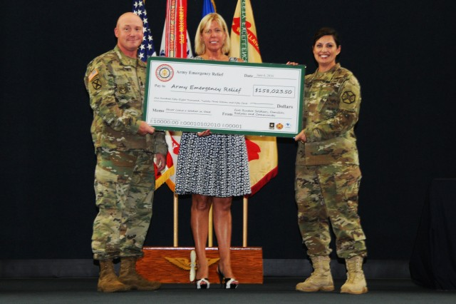 Col. Shannon T. Miller, Fort Rucker garrison commander, and Command Sgt. Maj. William D. Lohmeyer, Fort Rucker command sergeant major, present a check to Beth Gunter, AER program manager, during the AER closing ceremony at the U.S. Army Aviation Museum June 6.