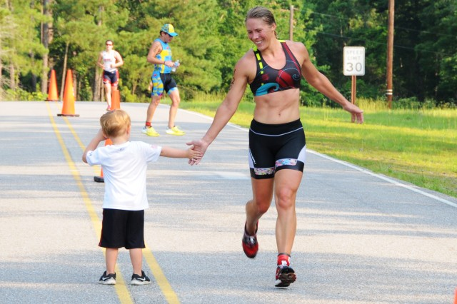 Sandy Johnson, civilian participant, gives Lucca Fischer, military family member, a high five as she rounds the corner to finish up her 3.1-mile run during the Army Strong Triathlon on West Beach at Lake Tholocco June 11.