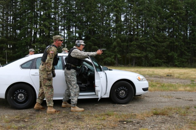 Staff Sgt. Jason Keller, military policeman with 42nd Military Police Brigade, observes and instructs a junior MP during a stress fire lane at Joint Base Lewis-McChord, Washington June 14, 2016. The stress fire training exercise took place as part of the Protector Professional Police Academy, a thirty day school MPs are required to complete in order to conduct street patrols and roadwork.
