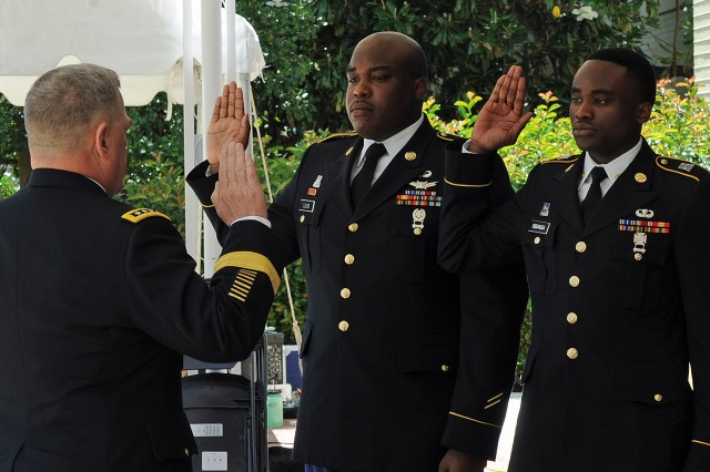 Army Chief of Staff Gen. Mark Milley gives the oath of enlistment to Sgt. Justin Louis and Spc. Jan BBanga during a cake-cutting celebrating the Army's 241st birthday at the Pentagon on June 17, 2016.