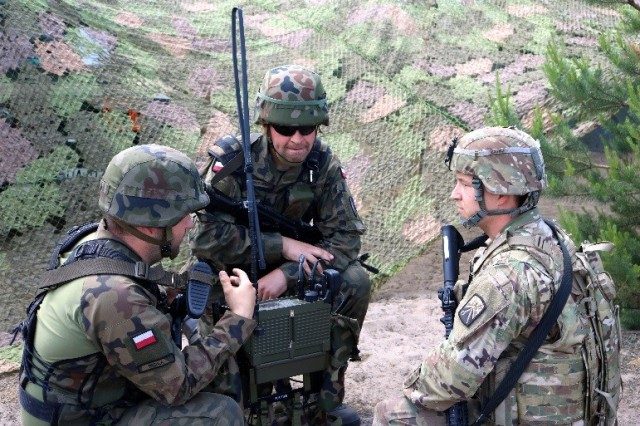 TORUN, Poland -- Sgt. Joshua Elkins (right), a nodal network systems operator assigned to the 504th Brigade Signal Company, 16th Special Troops Battalion learns how to use a Polish radio June 8. (Photo by 1st Lt. Hilary Klotz, 16th Sustainment Bde. Public Affairs)