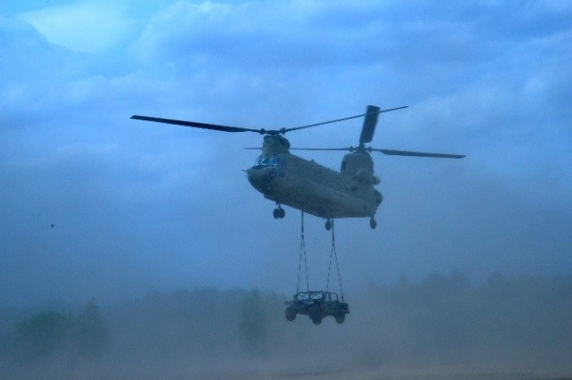 TORUN, Poland -- A 12th Aviation Brigade Chinook helicopter carries a humvee that was prepped and loaded by Soldiers from the 240th Quartermaster Supply Company, 18th Combat Sustainment Support Battalion. (Photo by Sgt. Daniel Wyatt, 16th Sustainment Bde. Public Affairs)
