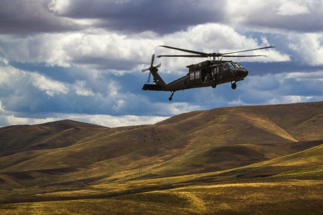 U.S. Army UH-60M Black Hawk helicopter Pilots and Crew Chiefs, assigned to 16th Combat Aviation Brigade, 7th Infantry Division, fly overhead during training at Yakima Training Center, Wash., June 16, 2016. The Black Hawk was used to sling load a UH-1 Huey helicopter as part of downed aircraft recovery team training.