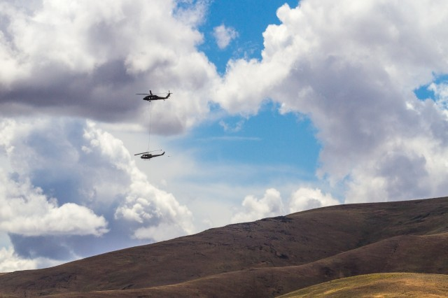 U.S. Army UH-60M Black Hawk helicopter Pilots and Crew Chiefs, assigned to 16th Combat Aviation Brigade, 7th Infantry Division, fly overhead carrying a UH-1 Huey helicopter during training at Yakima Training Center, Wash., June 16, 2016. The Black Hawk was used to sling load the Huey as part of downed aircraft recovery team training.