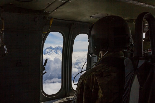 A U.S. Army Crew Chief, assigned to 16th Combat Aviation Brigade, 7th Infantry Division, looks out at the top of Mount Rainier, the highest peak in Washington, en route to training at Yakima Training Center, Wash., June 16, 2016. A UH-60M Black Hawk helicopter was used to sling load a UH-1 Huey helicopter as part of downed aircraft recovery team training.