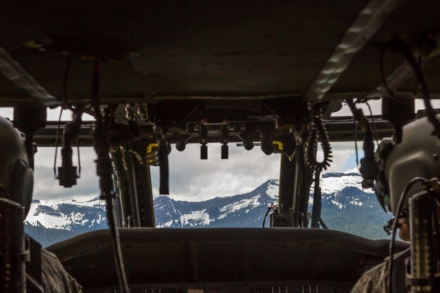 U.S. Army UH-60M Black Hawk helicopter Pilots, assigned to 16th Combat Aviation Brigade, 7th Infantry Division, fly near Snoqualmie Pass en route to training at Yakima Training Center, Wash., June 16, 2016. The Black Hawk was used to sling load a UH-1 Huey helicopter as part of downed aircraft recovery team training.
