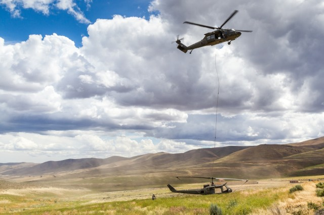 U.S. Army UH-60M Black Hawk helicopter Pilots and Crew Chiefs, assigned to 16th Combat Aviation Brigade, 7th Infantry Division, release a UH-1 Huey helicopter during training at Yakima Training Center, Wash., June 16, 2016. The Black Hawk was used to sling load the Huey as part of downed aircraft recovery team training.