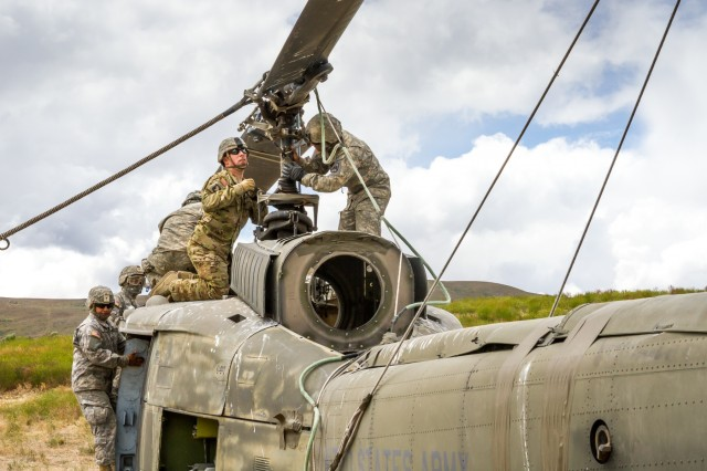 U.S. Army Soldiers, assigned to 16th Combat Aviation Brigade, 7th Infantry Division, secure equipment on a UH-1 Huey helicopter during training at Yakima Training Center, Wash., June 16, 2016. A UH-60M Black Hawk helicopter was used to sling load the Huey as part of downed aircraft recovery team training.