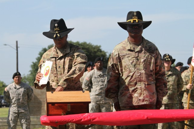 "Lt. Col. Lynn Ray, the first Regimental Engineer Squadron ""Pioneer,"" 3rd Cavalry Regiment commander, (left) places troop change of command programs to show the evolution of leadership within the Squadron inside of a wooden time capsule June 16, during the first birthday ceremony for the Regimental Engineer Squadron ""Pioneer,"" 3rd Cavalry Regiment at Fort Hood, Texas.  (Photo by Staff Sgt. Tomora Clark, 3rd Cav. Regt. Public Affairs)"