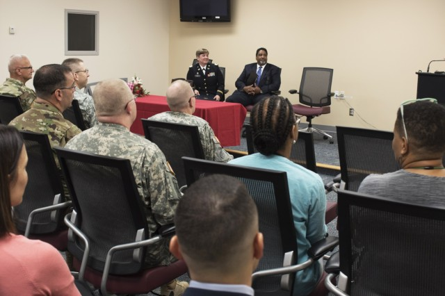 Col. Christopher Headrick, the 80th Training Command's Staff Judge Advocate, addresses the audience during a ceremony where Capt. Tanya Mayes, an administrative law and military justice attorney assigned to the 80th Training Command, received the 2015 American Bar Association's Legal Assistance for Military Personnel Distinguished Service Award. Retired Navy Captain Dwain Alexander, (seated next to Mayes) a member of the ABA LAMP committee, presented Mayes with the award at the Hunter Holmes McGuire VA Medical Center June 10, 2016. Mayes was recognized for leading an effort to establish a free legal assistance clinic for military veterans after she learned that a significant number of patients needed assistance.