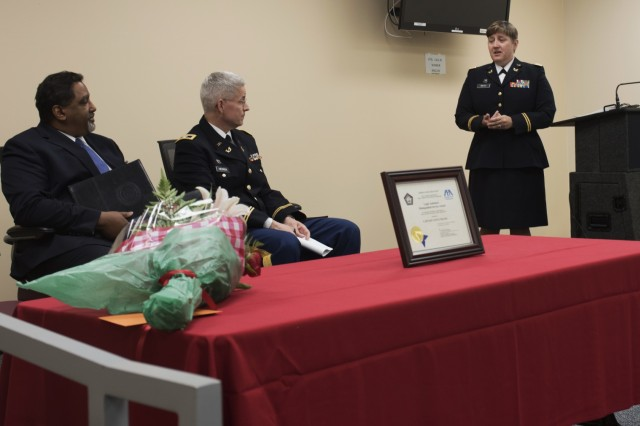 Capt. Tanya Mayes, an administrative law and military justice attorney assigned to the 80th Training Command, addresses the audience during a ceremony where she received the 2015 American Bar Association's Legal Assistance for Military Personnel Distinguished Service Award. Retired Navy Captain Dwain Alexander, (seated left) a member of the ABA LAMP committee, presented Mayes with the award at the Hunter Holmes McGuire VA Medical Center June 10, 2016. Mayes was recognized for leading an effort to establish a free legal assistance clinic for military veterans after she learned that a significant number of patients needed assistance. Seated next to Alexander is Col. Christopher Headrick, the 80th Training Command's Staff Judge Advocate.