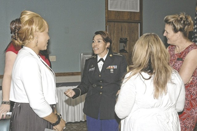 LGBT observance guest speaker, Command Sgt. Maj. Alma Zeladaparedes, center, visits with community members prior to the event.