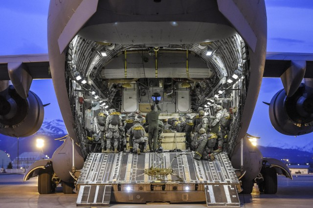 Paratroopers board and position their gear inside an Air Force C-17 Globemaster III aircraft before participating in a night jump at Joint Base Elmendorf-Richardson, Alaska, March 31, 2016.