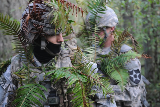 Spc. Spencer Secord, right, an intelligence analyst assigned to D Company, 14th Brigade Engineer Battalion, 2-2 ID, helps camouflage Sgt. Alfredo Munoz, a cryptologic linguist also assigned to D Company during a cyber training exercise at Joint Base Lewis McChord, Oct. 20, 2015.