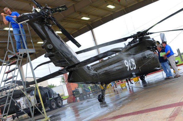 Workers at Lowe Army Heliport work together to clean a UH-60 Black Hawk June 15 using the more efficient water nozzles.
