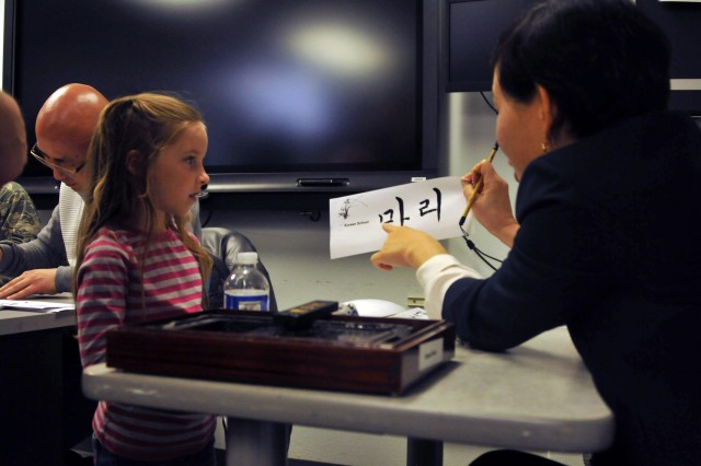 "PRESIDIO OF MONTEREY, California -- Yeohyun Sung, a DLIFLC Korean teacher, reads Marie Castrillo her name after writing it in Korean during a calligraphy demonstration during the Defense Language Institute Foreign Language Center's Language Day May 13, 2016 . Photo by Catherine Caruso, Presidio of Monterey PAOMore info: Thousands turned out for demonstrations of Palestinian fashion, Korean fan dancing, Russian pop music and other global cultural traditions during the Defense Language Institute Foreign Language Center's Language Day May 13, 2016 at the Presidio of Monterey. The annual event supports the military language school's motto: ""Peace through understanding,"" underscoring the importance of language education for thousands of high school students every year."