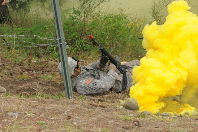 Sgt. James Buco, health care specialist, 62th Medical Brigade, moves passed concealment smoke in route to crawling below 15-feet of barbed wire as part of a Expert Field Medical Badge on Joint Base Lewis McChord, Wash., June 20. The competitors were challenged with communications skills, warrior tasks, medical evacuation and reacting to direct fire while moving through the lanes.