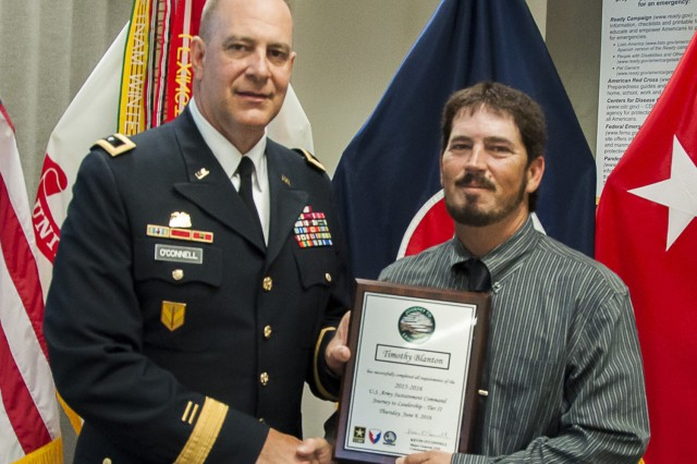 Maj. Gen. Kevin O'Connell, commanding general, U.S. Army Sustainment Command, presents Timothy Blanton, Logistics Readiness Center-Stewart, with a plaque following his graduation from Journey to Leadership Tier II at Rock Island Arsenal, Illinois, June 9. (Photo by Kevin Fleming, ASC Public Affairs)