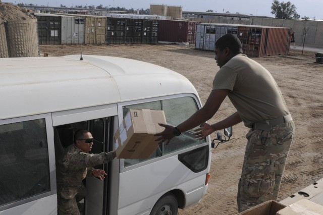 Spc. Edgar Cadiz (left), an automated logistics specialist with the 24th Composite Supply Company, throws a box of Iraq Train and Equip Fund supplies to Spc. Neil Bernard, an automated logistics specialist with the 24th CSC, March 9, 2016 in Iraq. Over the last few months and in conjunction with other units, Soldiers from the 24th CSC based out of Joint Base Lewis-McChord have overseen the distribution of hundreds of millions of dollars of ITEF supplies.