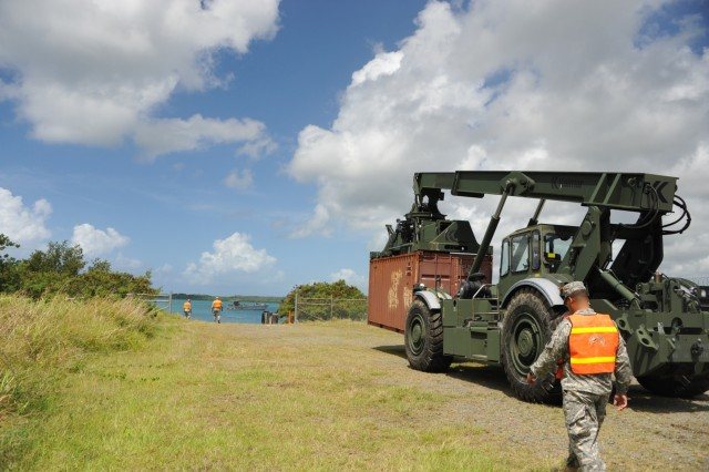 The operator of the RTCH, Sgt. Kris Gutierrez, 390th SPOC, is moving towards the LCM to place the container on it. On the corner right is PFC Luis Arzon assisting the operator.