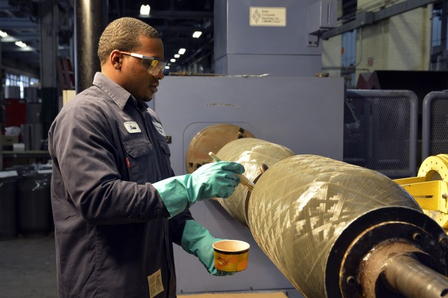 Metal Processor Sean Stephenson is apply a sealant to bore evacuators for the Abrams tank system.  For decades, the arsenal has manufactured bore evacuators for the Abrams tank system and now, the arsenal will add 155 mm bore evacuators to its product line.