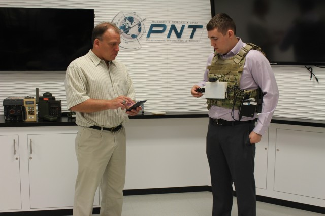 U.S Army CERDEC engineers Dr. Gary Katulka (left) and Eric Bickford (right),  demonstrate a vision-aided navigation laboratory-prototype system for dismounted Soldiers, which consists of the camera sensor head with integrated inertial measurement units, a general processing unit, and a battery pack (worn by Bickford), with associated control device  for Wi-Fi interfacing, system control, and data analysis (held by Katulka).
