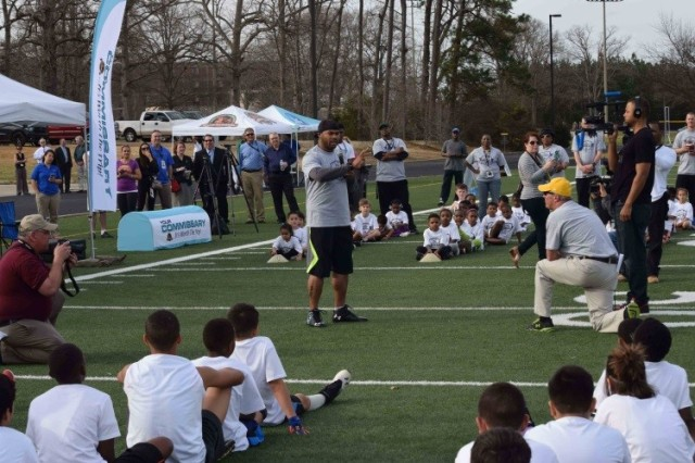 Baltimore Ravens, wide receiver Steve Smith talks to children at a 2015 ProCamp event in Fort, Lee, Virginia. From March through April, nearly 100 Installations competed for the opportunity to host a free, two-day ProCamp for first through eighth grade youth of active duty military, reservists, retirees, and DOD civilian employees. The 11 winning military installations qualify for a camp based on their patrons' purchases of select items in their local commissaries (DeCA photo: Rick Brink.)