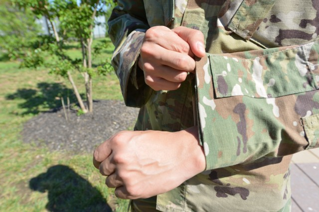 """A Soldier demonstrates how ACU sleeves can be tucked or cuffed inside for field operations in what is sometimes referred to as the """"Delta Roll."""""""