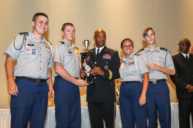 Brig. Gen. Sean Gainey, Deputy Commanding General for U.S. Army Cadet Command, presents the first place trophy to the Army Academic team from Lyman High School, Longwood, Fla., during the JROTC Leadership and Academic Bowl (JLAB) at The Catholic University of America, Washington, DC, June 27. Members of the team, from left to right were Joshua Toth, Anthony Del Palazzo, Angelica Sharkey and Jordan Franks.