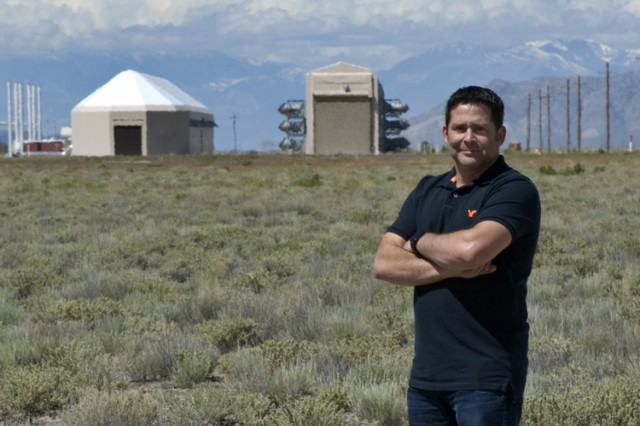 John Gomes, test officer with West Desert Test Center's Special Programs Division at U.S. Army Dugway Proving Ground, Utah. Gomes stands before the Active Standoff Chamber (left) and Joint Ambient Breeze Tunnel. Both test facilities will be used during the Aug. 2016 S/K Challenge that invites manufacturers and developers of chemical and biological detectors to test their instruments against simulated agents. (Photo by Al Vogel / Dugway Public Affairs)