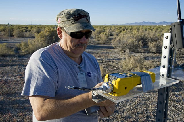 A participant in the 2014 S/K Challenge secures a portable chemical agent detector to a fixture, prior to the release of a chemical simulant. Outdoor testing realistically challenges a detector's capabilities, providing data to defend against a real attack or chemical incident in an urban or rural setting. (Photo by Al Vogel, Dugway Public Affairs)